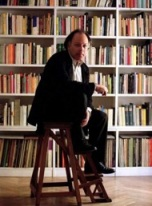 Javier Marias sitting on stool in front of wall of books